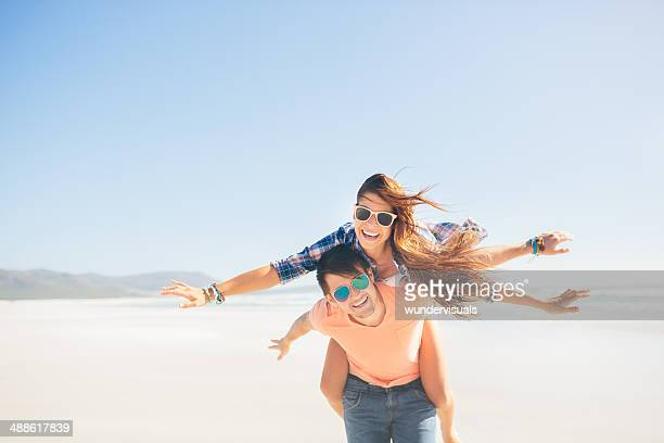 Couple piggyback on beach