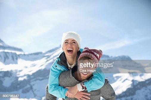 Couple piggybacking at mountains