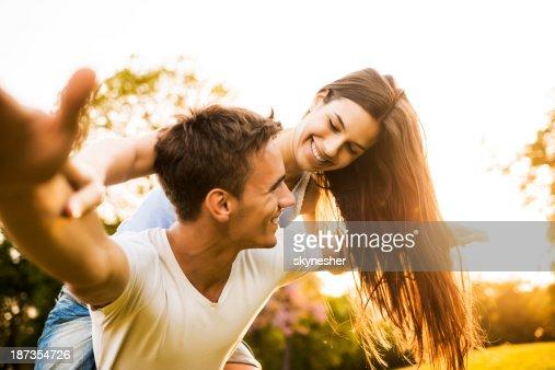 Couple piggybacking at sunset.