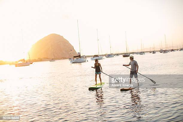 Couple pilot paddle-boards across bay, near marina