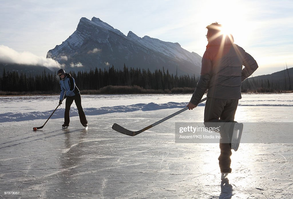 Couple play hockey on pond ice, mtns : Stock Photo