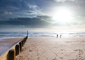 'Bournemouth Beach, a couple play and dance on the shoreline in the sunset, a tidal break leads the eye into the scene'