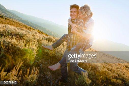 Couple playfully piggybacking through field. : Stock Photo