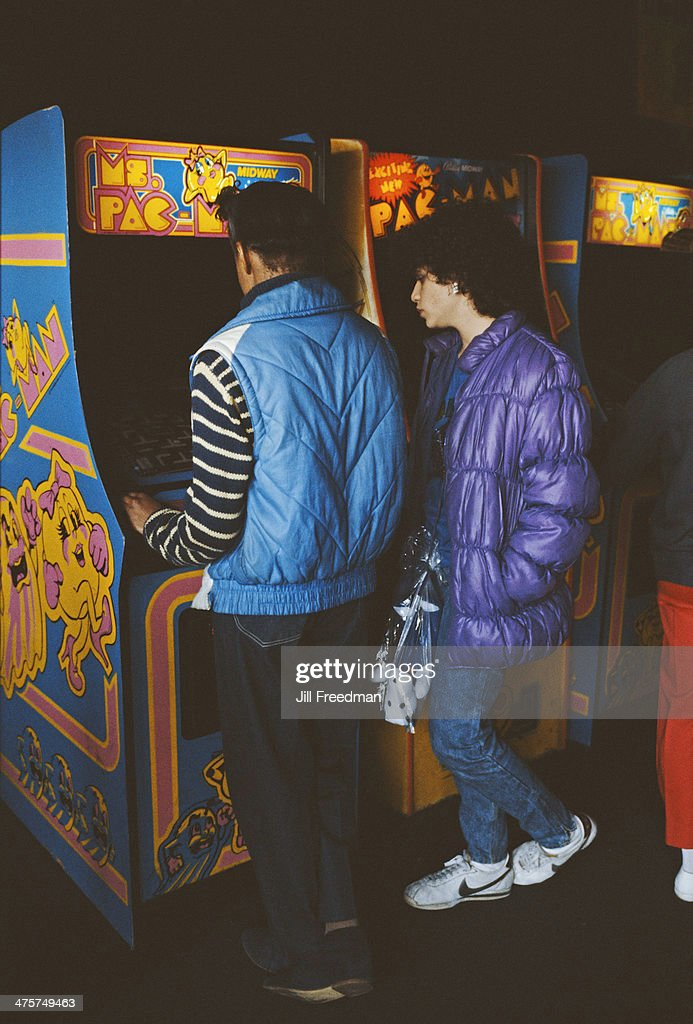 A couple playing arcade games, namely Ms Pac-Man, New York City, circa 1985.