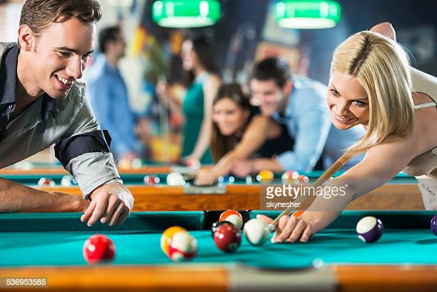 Couple playing billiard.