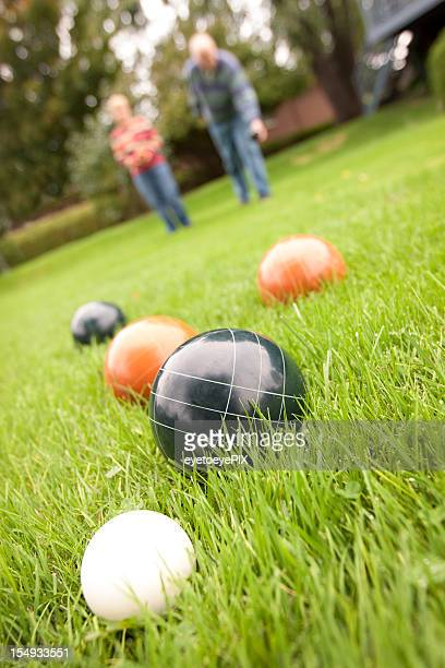 Couple playing bocce ball in grass