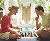 Couple playing chess by swimming pool, side view