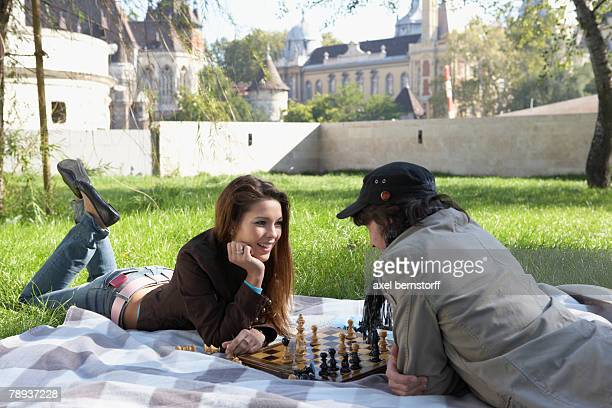 Couple playing chess in a park smiling.
