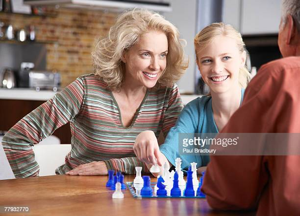 Couple playing chess with girl