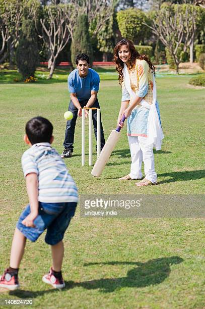 Couple playing cricket with their son, Gurgaon, Haryana, India