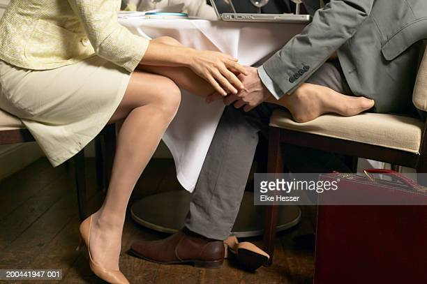 Couple playing footsie under restaurant table