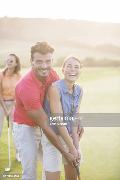 コースでゴルフをお楽しみのカップル