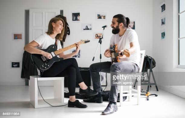 Couple playing guitars