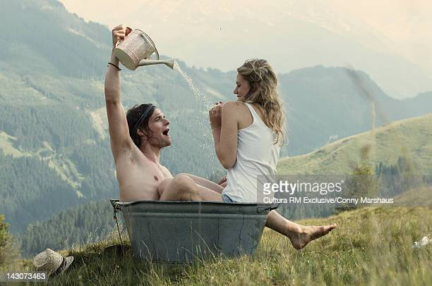Couple playing in metal tub outdoors