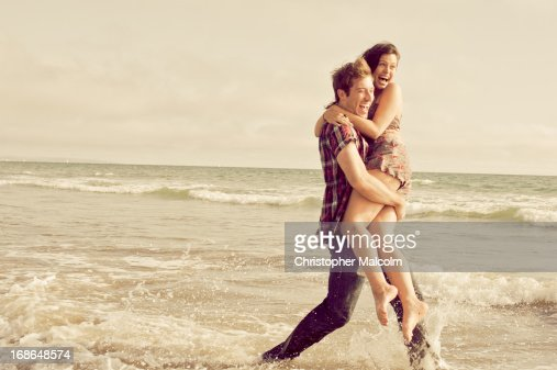 Couple playing in ocean : Stock Photo