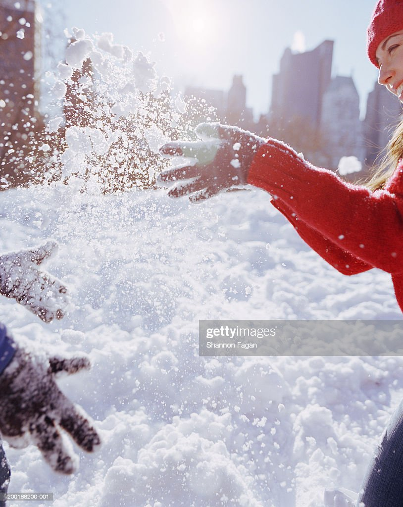 Couple playing in snow, woman smiling : Stock Photo