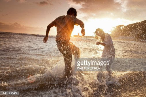 Couple playing in waves at beach : Stock Photo