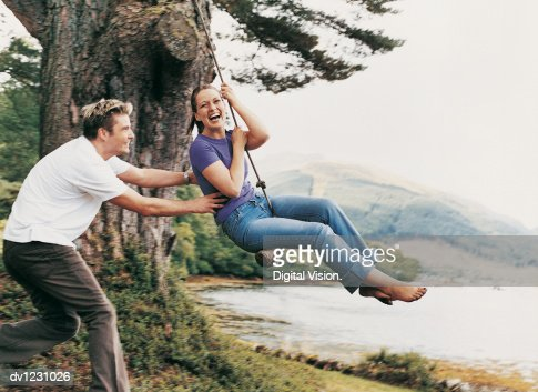 Couple Playing on a Rope Swing, Man Pulling Woman : Stockfoto