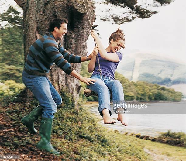 Couple Playing on a Rope Swing, Man Pushing Woman