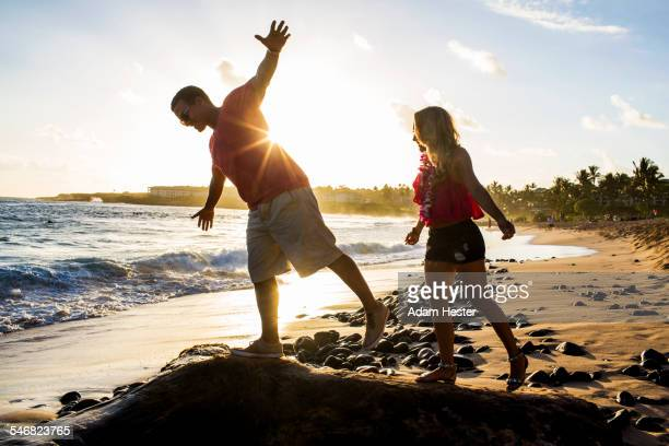 Couple playing on rocks on beach