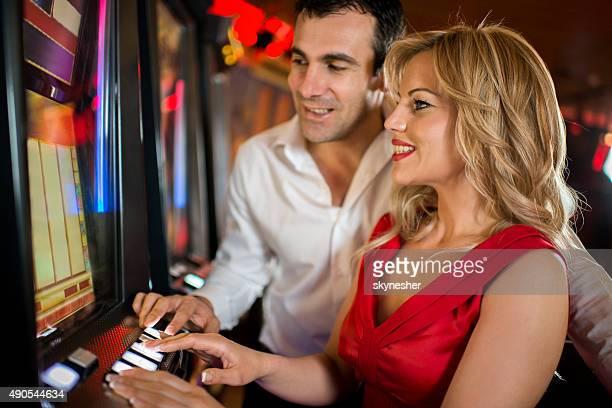 Coppia giocano a slot machine del casinò.