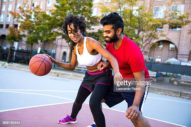 Couple playing outdoor at city basketball court