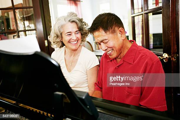 Couple playing piano together in living room