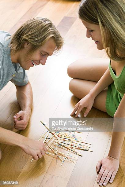 Couple playing pick up sticks together