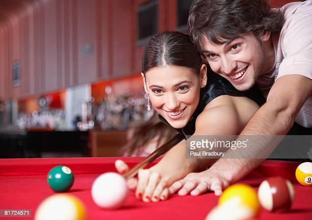 Sonriente pareja jugando con piscina y