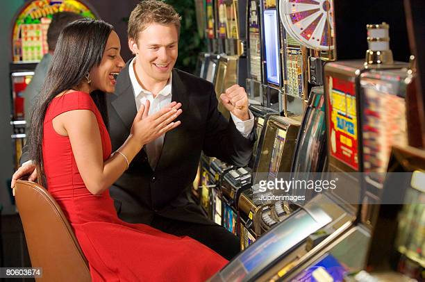 Couple playing slot machine