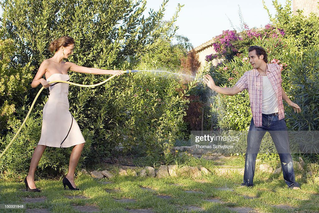 A couple playing with a hose and water outdoors : Stock Photo