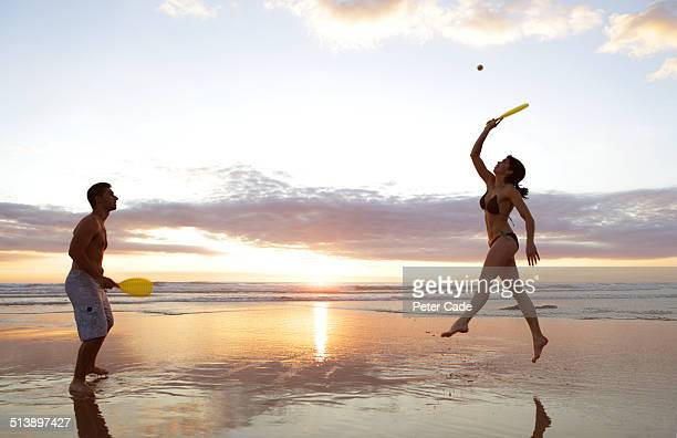 Couple playing with bat and ball on beach at sunet