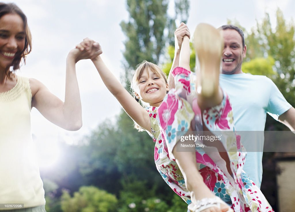 Couple playing with daughter (8-9) in garden : Stock Photo
