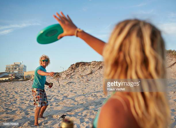 Couple playing with frisbee on the beach