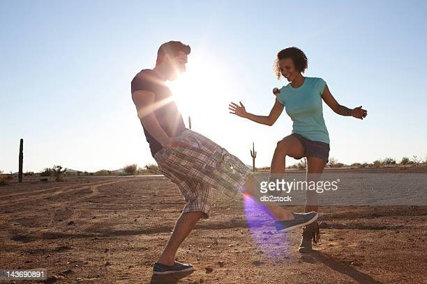 Couple playing with hackey sack outdoors