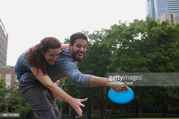 Couple playing with plastic disc in urban park