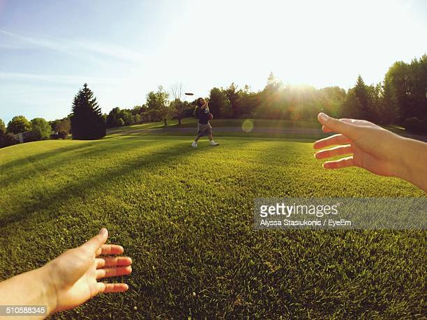 Couple playing with plastic disc on grassy field