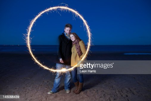Couple playing with sparkler on beach : Stock Photo