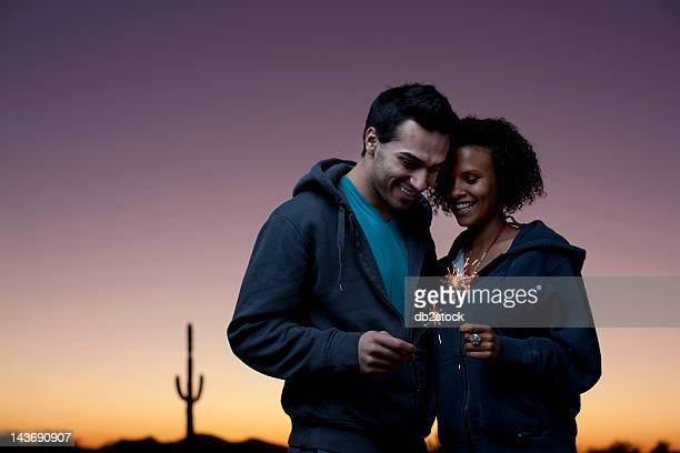 Couple jouant avec cierges magiques dans le désert