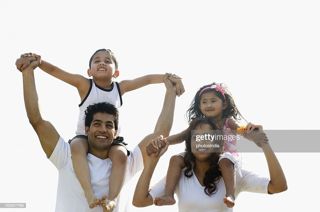 Couple playing with their children : Stock Photo