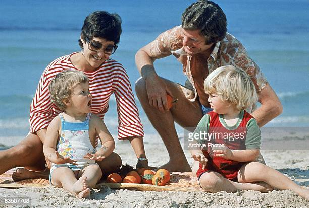 A couple playing with their infant daughter and son on the beach 1970s