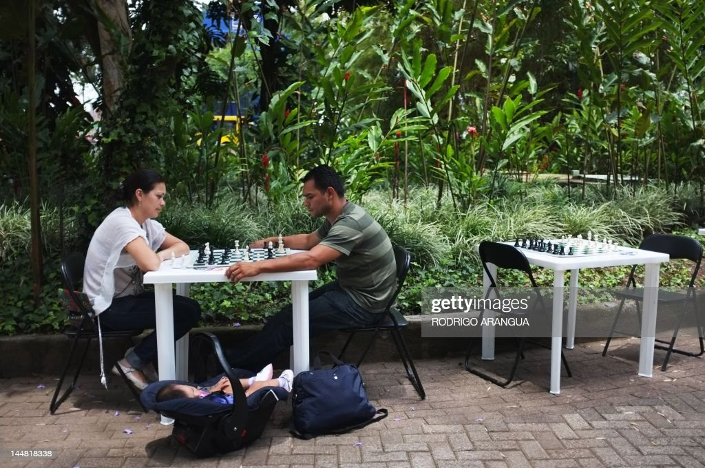A couple plays chess at Spain square in San Jose, on May 19, 2012. The Costa Rican Ministry of Culture and Youth is launching cultural activities under the slogan 'Fall in love with your city', such as art workshops, music, theater, dance, and traditional games, that take place every Saturday in different parts of downtown San Jose. AFP PHOTO/Rodrigo ARANGUA /