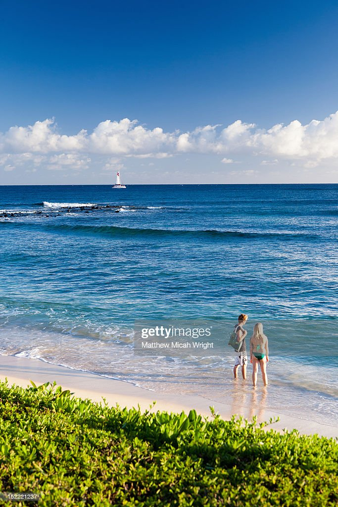 a couple plays in the shallow ocean water stock photo
