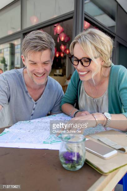 Couple pointing at map on city sidewalk cafe table