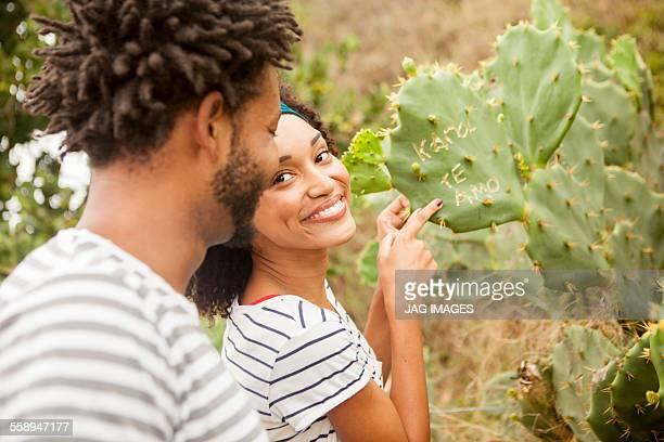 Couple pointing to names on cacti leaf, Ipanema beach, Rio De Janeiro, Brazil