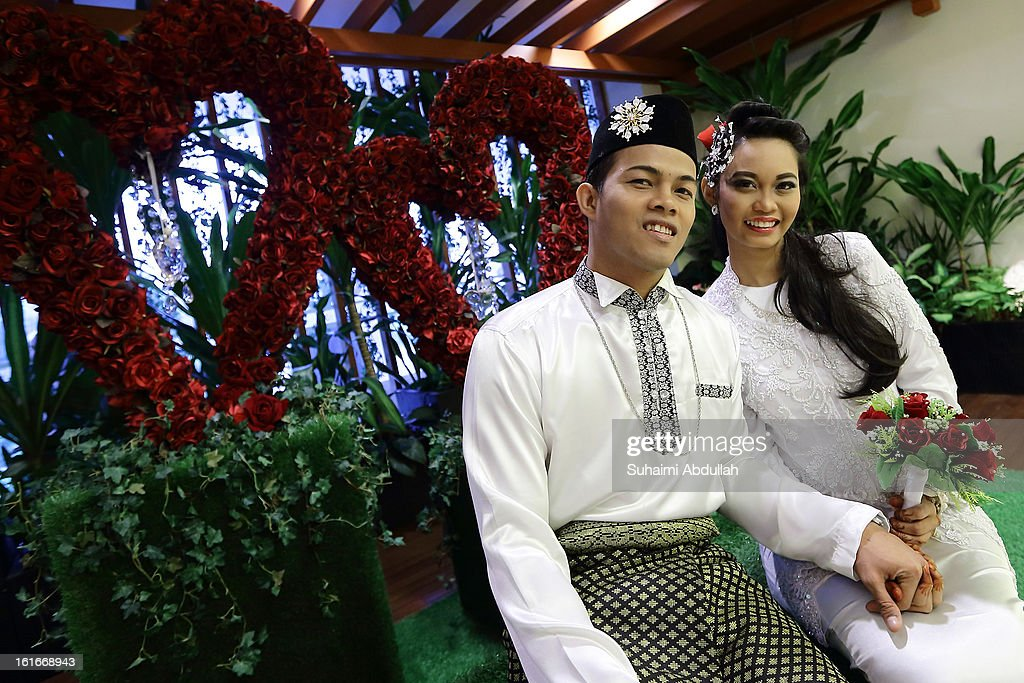 A couple pose for a photo at the Registry of Marriages at Fort Canning on 14 February, 2013 in Singapore. Couples take advantage of Valentine's Day to tie the knot on the day of love, to make it more memorable. Valentine's Day is a time to celebrate love, romance and friendship and is celebrated worldwide annually in different ways on February 14.