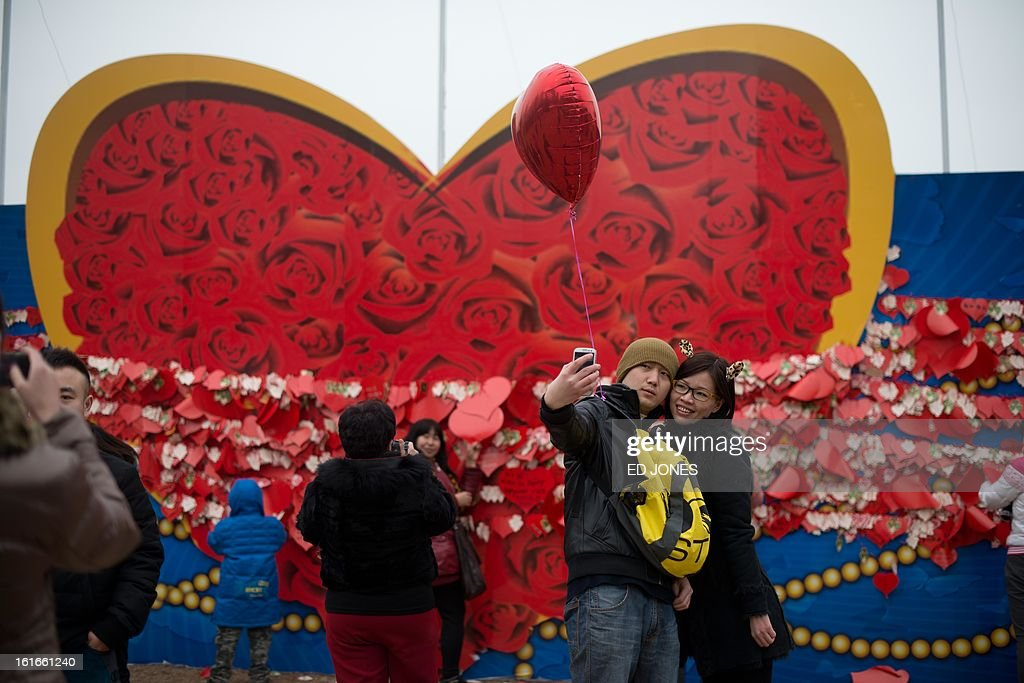 A couple pose for a photo before a heart-shaped backdrop at a park in Beijing on Febraury 14, 2013. Businesses in the Chinese capital were said to be fearing the proximity of Chinese Lunar New Year falling just days before Valentine's day, after some nine million Beijingers were reported to have left the city for the annual holiday exodous, according to state media. AFP PHOTO / Ed Jones