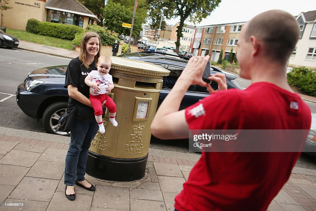 A couple pose for a photograph in front of a gold post box in Isleworth on August 6, 2012 in London, England. The post box was painted gold to celebrate British athlete Mo Farah's victory in the Men's 10,000m race at the London 2012 Olympic Games on Saturday and is located close to where Mo trained and went to school.
