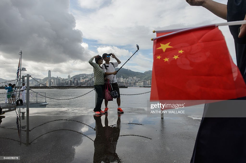 A couple pose for a selfie during the open day of the Chinese People's Liberation Army (PLA) Navy Base at Stonecutter Island in Hong Kong on July 1, 2016, to mark the 19th anniversary of the Hong Kong handover to China. / AFP / Anthony Wallace