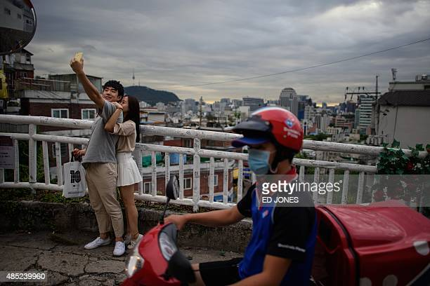 A couple pose for a 'selfie' photo as a pizza delivery courier rides past on a scooter at a viewpoint overlooking the city skyline in the Hyehwa...